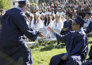 From left, Miles Johansen slaps hands with fellow graduating classmate Victor Andrade during North Tahoe High commencement ceremony.