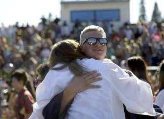 Ryan Conner and a fellow North Tahoe High School graduate hug after Thursday's commencement ceremony at Laker Stadium.