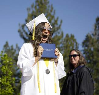 North Tahoe High graduate Kasey Foster is thrilled to accept her diploma, while school principal Joanna Mitchell looks on at the June 11 ceremony.
