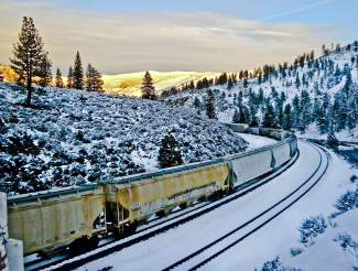 Snow Locomotive: A train is pictured traveling along the Truckee River, with a sunny Mount Rose Wilderness in the background.