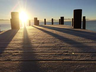 Shooting on the Dock of the Bay: Morning sun shines down on a frozen dock on the west shore of Lake Tahoe.