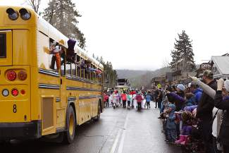 Spectators line Highway 28 for the Tahoe City SnowFest! Parade, watching and waving as various groups and vehicles pass by such as this Tahoe Truckee Unified School District bus filled with area students.