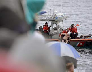 The U.S. Coast Guard pulls a male participant of Saturday's Polar Bear Swim out of the cold waters of Lake Tahoe and into a boat.