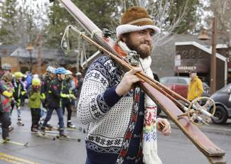 Brian Sidenberg, from Hauserman Rental Group, represents the group and the Cobblestone Shopping Center in the Tahoe City SnowFest! parade. Those representing Tahoe City-based Tahoe Cross Country can be seen behind him.