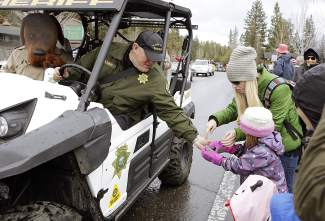 Placer County Sheriff officials hand out candy to children lining Highway 28 in Tahoe City during Saturday's parade.