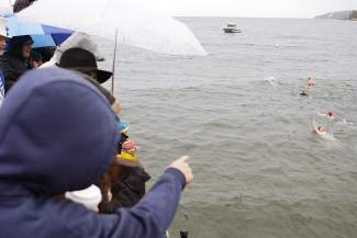 Onlookers crowd the pier at Gar Woods to watch and cheer those participating in the Polar Bear Swim.