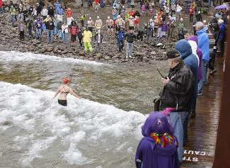 A female participant of the Gar Woods Polar Bear Swim comes out of Lake Tahoe after completing the lap as onlookers watch on Saturday afternoon.
