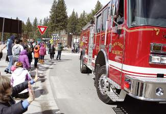 People in the crowd clap and wave as North Tahoe Fire Protection District fire trucks drive past as part of Saturday's parade in Kings Beach.