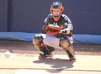 San Francisco Giants catcher Buster Posey warms up Jake Peavy in the bullpen before the start of a Spring Training game in Peoria.