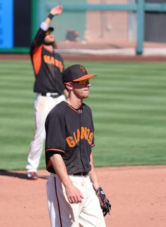 Giants shortstop Brandon Crawford, background, checks the glare of the sun as Matt Duffy readies for a pitch at Spring Training.