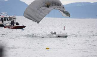 A member of the Guardian Angels of the 129th Rescue Wing safely lands in the waters of Lake Tahoe on Sunday afternoon as part of a search and rescue demonstration.