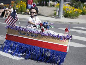 Sailing down Tahoe Boulevard as part of Friday's Kid's Bike Parade, this boy uses his decorated bike to thank veterans.