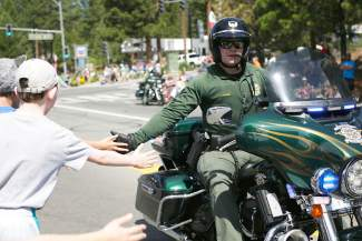 J. Fisher, with the Washoe County Sheriff's Office, slaps the hands of children lining Highway 28 in Incline Village on Friday morning during the Red, White and Tahoe Blue parade.