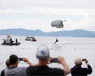 Those at Incline Beach gather to watch and take photos as a member of the Guardian Angels of the 129th rescue wing of the California Air National Guard parachutes into the waters of Lake Tahoe on Sunday afternoon.