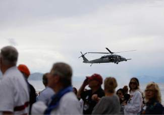 While the National Anthem is sung Saturday afternoon at Incline Beach, a helicopter carrying members of the 129th Rescue Wing of the California Air National Guard fly in the background.
