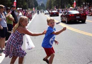 Two children try to catch thrown candy during Friday's Red, White and Tahoe Blue