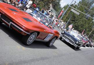 A procession of cars drives down Highway 28 Friday morning as part of Red, While and Tahoe Blue's annual parade.