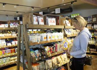 A patron of the West Shore Market & Deli examines its general grocery goods Sunday at the store's grand reopening.