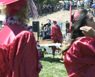 A student collects his diploma from science teacher Susan Lowder, while other students wait in line to collect their own Saturday morning at Truckee High School's graduation ceremony.