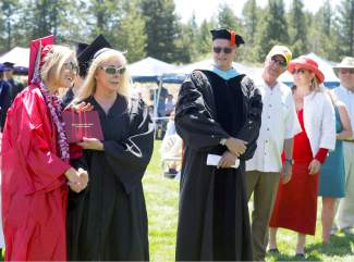 Truckee High School graduate Olivia Mousaw accepts her diploma from fine arts teacher Jan Moseley, as Tahoe Truckee Unified School District Rob Leri and TTUSD Board of Education members Randy Hill, Kirsten Livak, Dianna Driller and Gaylan Larson look on.