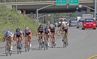 The women's field in the 17 to 18 age group crosses under Interstate 80 on their way from Loyalton to Northstar. One racer in the background waits for a support vehicle with a flat tire.