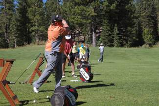 Participants of the Gene Upshaw Memorial Golf Classic take swings at the driving range before the tourament tees off.