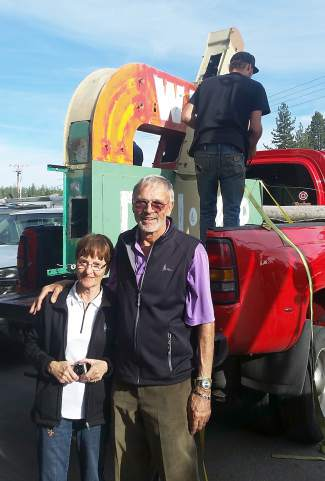 The donors for the sign restoration and the store's namesakes, Klaus and Gisela Zander, recently stand next to the sign as crews prepare to transport it for restoration.