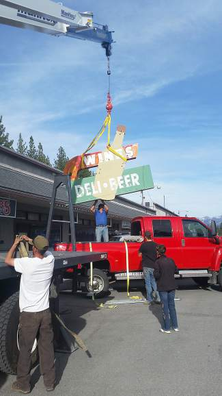 A crane recently lifts the refurbished, nearly 70-year-old sign that had become synonymous with what is now Zander's Spirits, Etc.