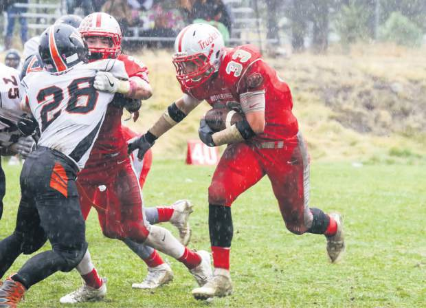 Truckee fullback Wulfe Retzlaff, right, moves the chains while Cole Harrity, left, makes a block on Fernley's Willy Pritchard during the Wolverines' 39-7 home win on a rainy Saturday at Surprise Stadium.