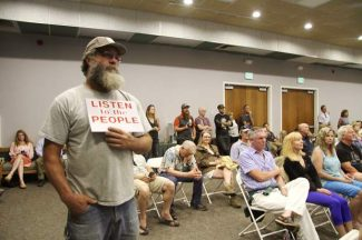 """A local resident holds a sign that says """"LISTEN TO THE PEOPLE"""" during the July 7 Placer County Planning Commission hearing of the Martis Valley West proposal. The commission voted 5-2 to recommend denial of the project, which was eventually approved 4-1 by the county's board of supervisors."""