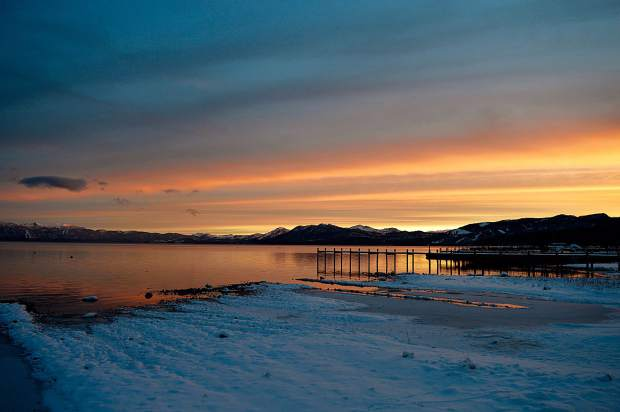 Picture Perfect: The sky burns orange over a snowy Lake Tahoe as seen in late December in Tahoe City.