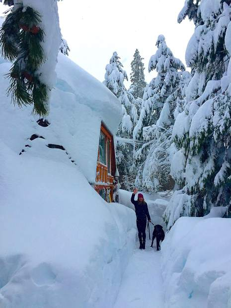 Can You Dig It: Kate and her dog, Mabel, are all smiles after digging out their Homewood ski hut in late January. Photo: Kate Allen-Rabinowitz