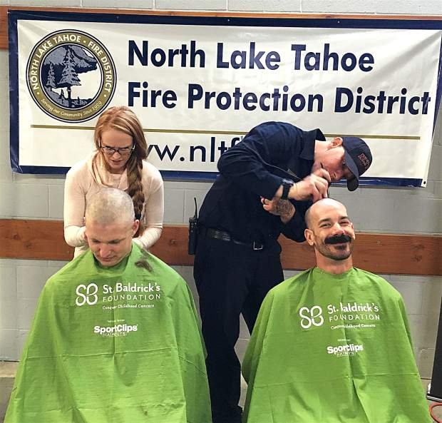 DONATIONS THAT MAKE A DIFFERENCE: In addition to the barbecue on March 10, a pre-shave event took place to support St. Baldrick's, which raises funds for childhood cancer research. Visit www.stbaldricks.org to learn more. Here, from left, Kathryn Phillips and Shane Schuster work to cut off the hair of Josh Phillips and Jason Kiesling.