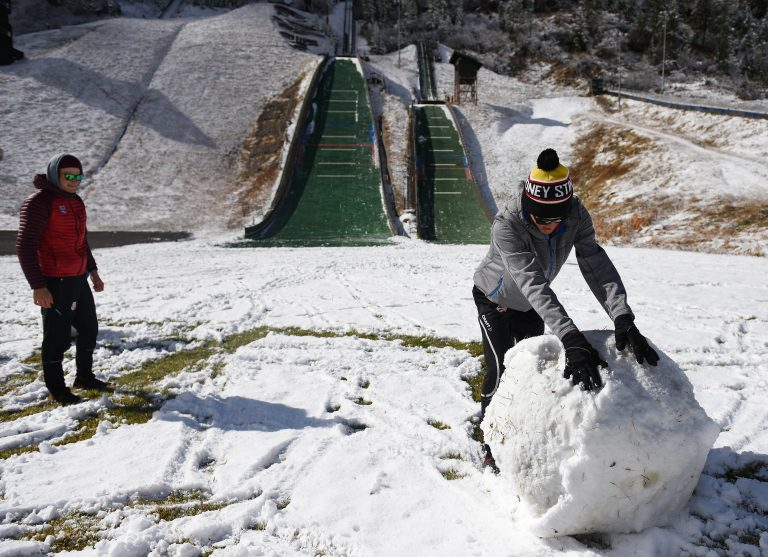 Jasper Good rolls what became the base of the U.S. Nordic Combined Ski Team's snowman on Saturday at Howelsen Hill.