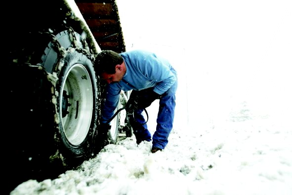 Man puts chains on his truck's tires for the snow.