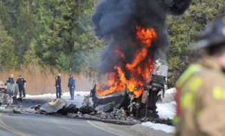 Firefighters watch as the burning fatal head on collision sends plumes of black smoke into the air above rural Highway 20 in Placer County Wednesday morning.
