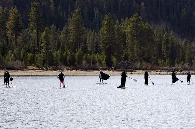 A coven of witches celebrates Halloween by stand-up paddle boarding across Donner Lake on Wednesday, Oct. 31.