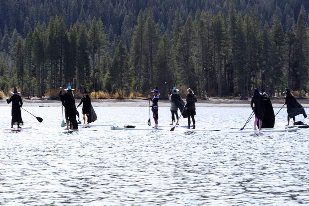 A coven of witches celebrates Halloween by stand-up paddle boarding across Donner Lake on Wednesday.