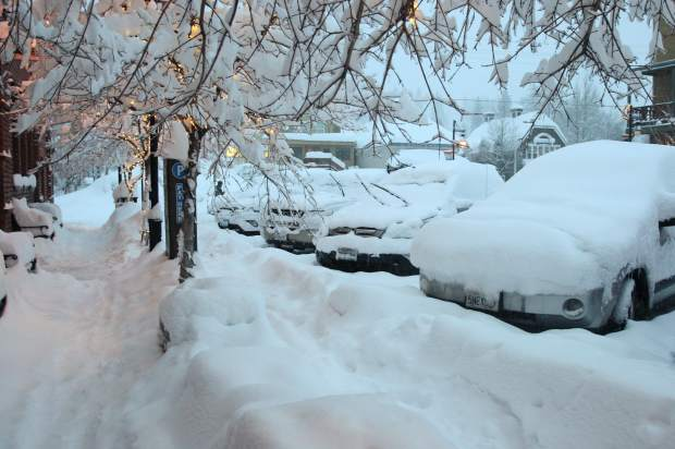 Cars sit buried in downtown Truckee with snow continuing to fall.