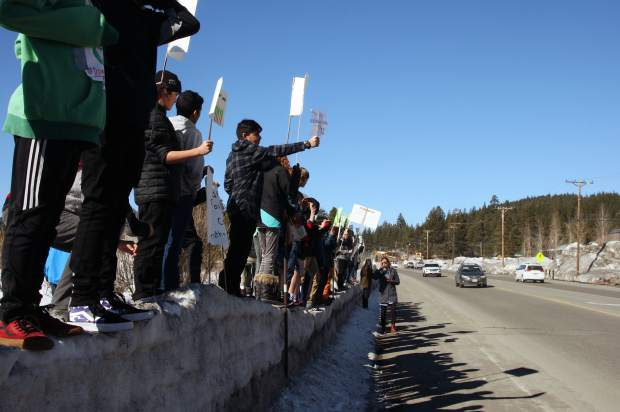 Passing cars honked and waved at students who lined a section of Donner Pas Road holding hand-made signs and chanting