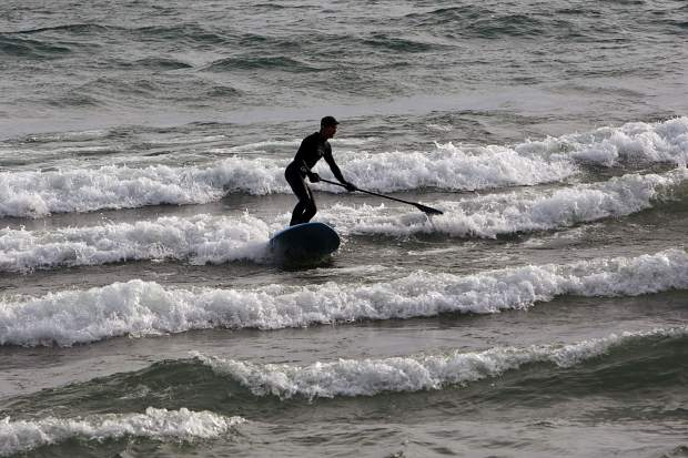 A paddleboarder rides toward the sand at Kings Beach as a set of spring storms roll into the area.