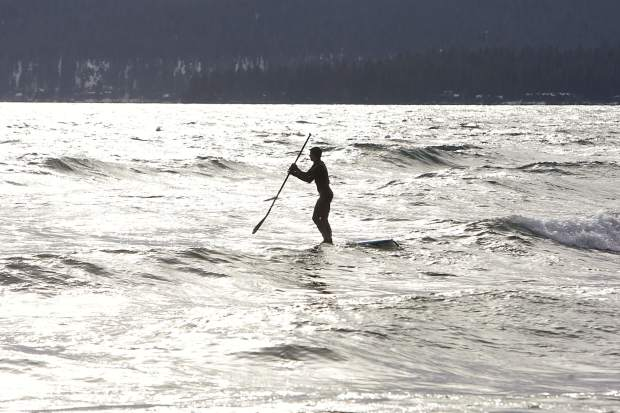 After catching a wave, a stand-up paddleboarder heads back out for another ride.