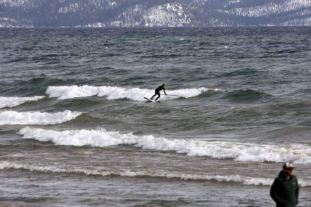 A paddleboarder catches a wave on Lake Tahoe on Monday, March 25.