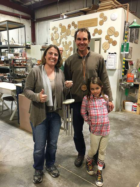 Sara and Volunteer Fixit Coaches Abe and Sawyer Haen with their newly repaired wind chimes.