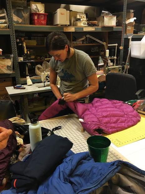 Patagonia repair team member Quinn Dannies patching a jacket.