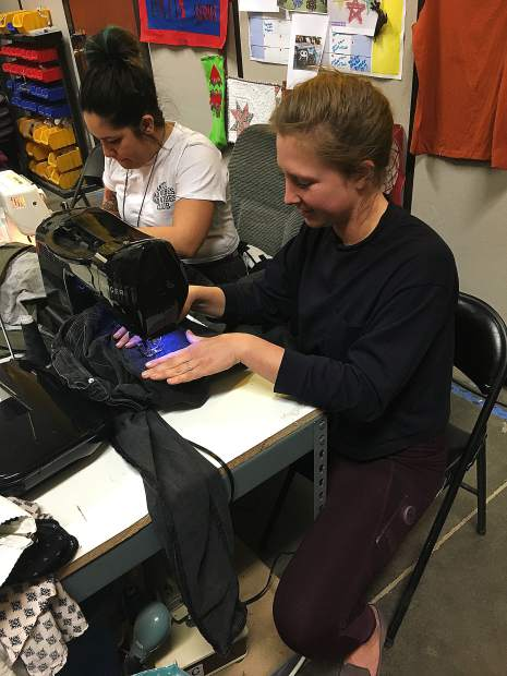 : Linnea Whitney repairing jeans on a sewing machine.