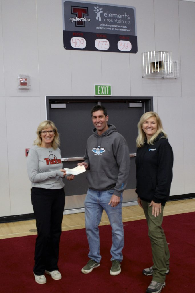 Elements Mountain Company presents Truckee Athletic Director Erika Murphy with a check for $773. The company donated $1 for each point scored during Truckee home basketball games this past season.
