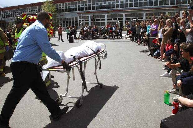 After public safety officials treated the injured students, their classmates watched as the coroner took the students away who had died in the accident.
