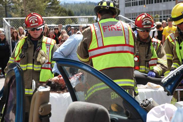 Firefighters pull two students from the wrecked car.