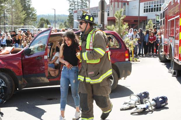 A firefighter helps an injured student to the ambulance.